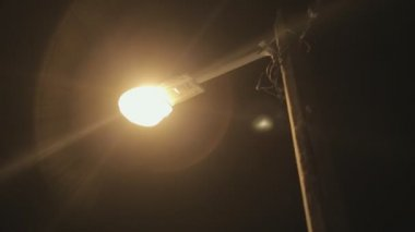 Ignited and fading  street-lamp at night on street — Stock Video