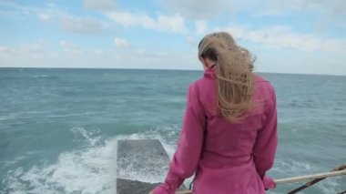 Girl in a pink coat walking on the pier stands during a storm at sea and looking — Stock Video