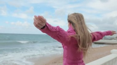 Blonde girl raises her arms up on the beach — Stock Video