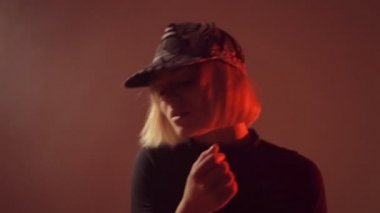 Girl in a cap moving in the studio in the smoke — Stok video