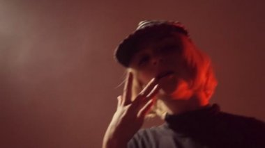 Girl in a cap moving in the studio in the smoke — Stock Video
