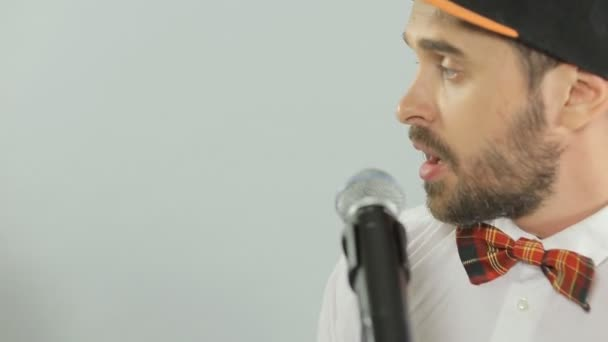 Trendy blue-eyed man with a mustache and beard sings into a microphone — Vidéo