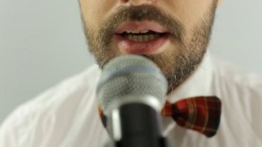Close up of mouth of the singer performs a song in a microphone on a white background — Stock Video