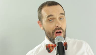 Close-up of a blue-eyed singer performs a song in a microphone on a white background — Stock Video