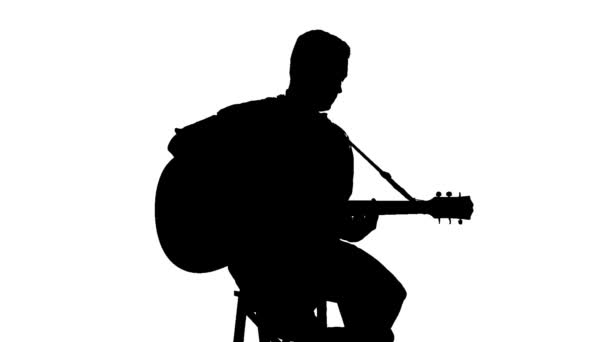 Silhouette of sitting man playing the guitar on a white background — Vidéo