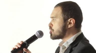 Close-up of a blue-eyed man with a beard wearing a jacket singing a song into the microphone in a studio — Stock Video
