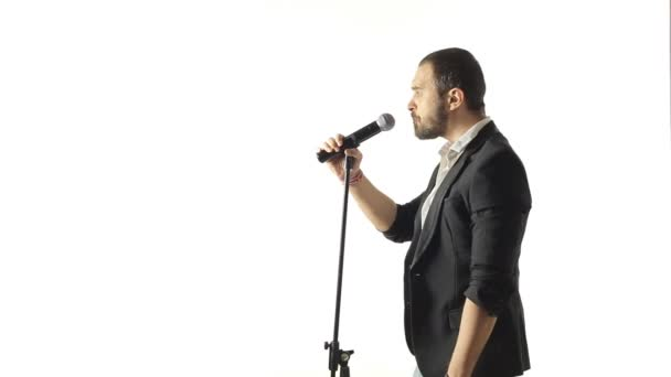 Handsome man performs a musical composition in the studio on a white background — Vidéo