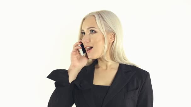 Beautiful blonde in a strict suit talking on a cell phone on a white background in studio — Vidéo