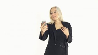 Sexy business woman fooling around and making selfie photo on a mobile phone on a white background — Stock Video