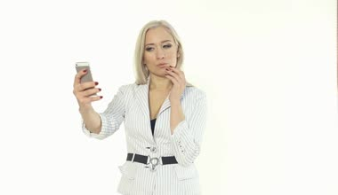 Business woman in a white jacket making selfie photo on the phone on a white background — Stock Video