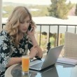 Beautiful young woman talking on the phone while sitting in a restaurant on the summer terrace in front of laptop — Stock Video #74100069