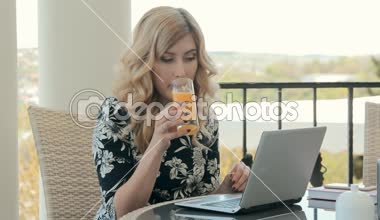 Attractive young woman drinking orange juice in a restaurant in the summer terrace and typing on a laptop — ストックビデオ
