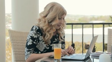 Attractive young woman typing on a laptop and drinking orange juice in a restaurant in the summer terrace — ストックビデオ