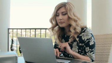 Beautiful woman with curls intently typing something on the laptop — Stock Video
