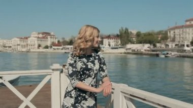 Charming young woman in dress standing on a wooden pier near the sea and smiling — Stock Video