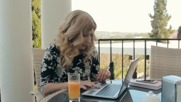 Attractive young woman working at a laptop in a cafe on the terrace — Vidéo
