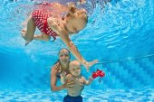 Baby underwater swimming lesson with instructor in the pool — Stock Photo