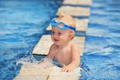 Happy child in blue goggles playing with water splashes in pool before swimming — Stock Photo