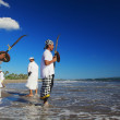 Balinese men with ritual swords on the sea shore — Stock Photo #73672297