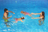 Children with parents swimming underwater in blue pool — Stock Photo
