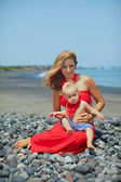Beautiful young mother with baby son have a fun on the Bali sea beach — Stock Photo