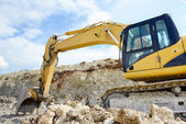Limestone quarry with earth mover — Stock Photo