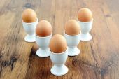 Five egg cups with natural brown eggs in arrow shape on table — Stock Photo