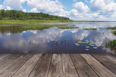 Timber floor of a terrace against the lake with the reflected clouds — Stock Photo