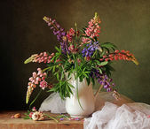Still life with a bouquet of lupines and a cockleshell. — Stock Photo