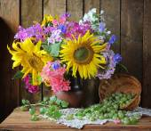 Still life with a bouquet of sunflowers and phloxes. Flowers and berries. — Stock Photo