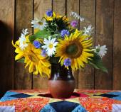 Still life with a bouquet of sunflowers, camomiles and cornflowers. Sunflowers. — Stock Photo
