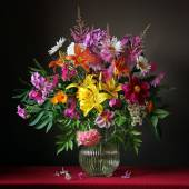 Bouquet from cultivated flowers in a jug on a red cloth — Stock Photo