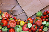 Fresh red and green tomatoes, segments of a cucumber and paper package — Stock Photo