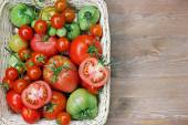 Fresh red and green tomatoes in a basket on a table — Stock Photo