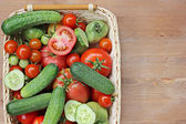 Fresh cucumbers, red and green tomatoes in a basket on a table — Stock Photo