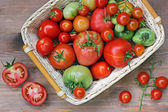 Fresh red and green tomatoes in a basket — Stock Photo