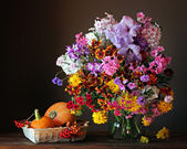Still life with a bouquet, pumpkins and berries — Stock Photo