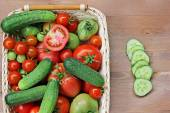Fresh cucumbers, red and green tomatoes  in a basket — Stock Photo