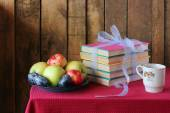 A still life with books, plums and apples. — Stock Photo