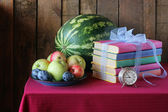 Still life with books for hours, plums, a water-melon and apples — Stock Photo