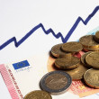 Euro coins and banknotes and rising chart line — Stock Photo #60949877
