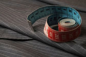 Classic striped gray suit coat and rolled measure tape — Stock Photo