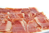 Closeup of spanish serrano ham on white background. — Stock Photo