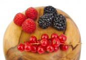 Blackberries, red currants and raspberries on a olive wood surface. — Stock Photo