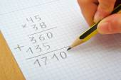 Hand of a child making a multiplication with a pencil. Math. School concept. — Stock Photo