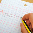 Closeup of the hand of a child writing apple word with a pencil. School concept.. — Stock Photo #64030243