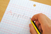 Closeup of the hand of a child writing apple word with a pencil. School concept.. — Stock Photo