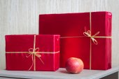 Red Gifts and apple. — Stock Photo