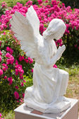 Statue of a praying angel on a background of blurred flowers. — 图库照片