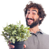Young bearded man with a plant — Стоковое фото